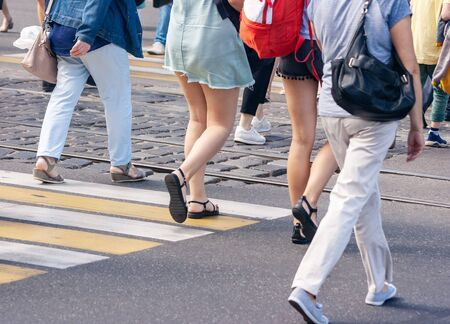 people crossing the street at pedestrian crossing on sunny spring day
