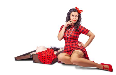 young pretty woman in red dress and nylon stockings sitting on the floor and putting clothes in a suitcase over white background. pinup style