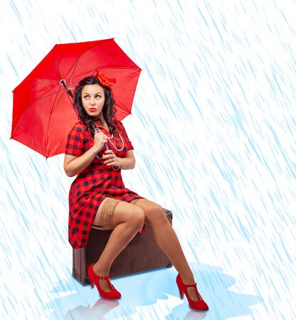 beautiful young woman in red dress and nylon stockings with red umbrella sitting on a suitcase with drawn stylized rain. pinup style