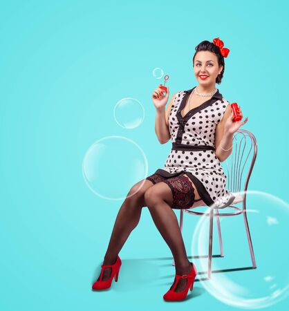 young beautiful smiling woman in white dress and black nylon stockings sitting on chair and blowing bubbles indoor over green background. pinup style Standard-Bild - 128104018