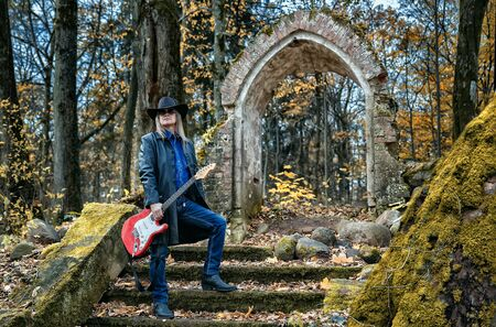 elderly long haired man in a leather coat, hat, sunglasses and jeans standing with an electric guitar in a dark forest near a ruined chapel