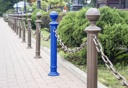 decorative fence made of metal posts in a city park on summer day. concept i am different from others Banco de Imagens