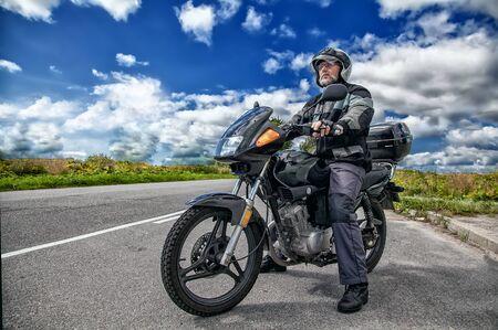 Motociclista anziano che indossa una giacca e occhiali con un casco seduto sulla sua moto su strada aperta nella soleggiata giornata estiva Archivio Fotografico