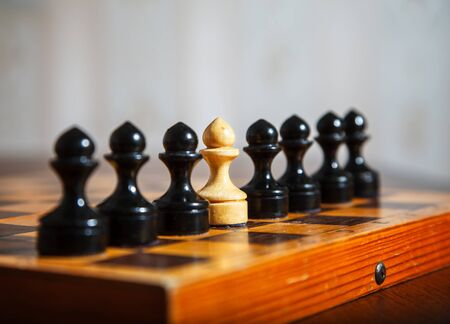 one white chess pawn standing in a row of black pawns on a chessboard. conept i am different from others