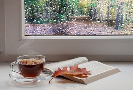 cup of coffee, an open holy bible and a red maple leaf on the windowsill with raindrops on the glass on gloomy autumn day