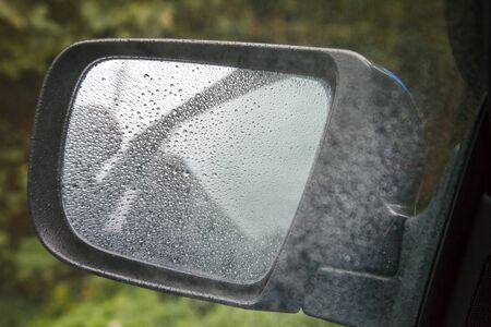 car mirror with raindrops outdoor closeup on gloomy rainy autumn day