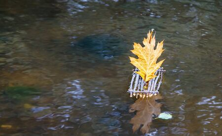 toy raft with a sail from maple leaf floating on the lake on autumn day