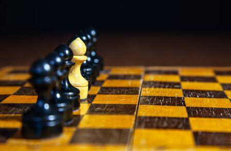 ein weißer Schachbauer, der in einer Reihe von schwarzen Bauern auf einem Schachbrett steht. Konzept ich bin anders als andere Standard-Bild