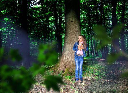 little scared girl in denim costume standing near the tree in the dark woods