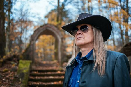 portrait of an elderly long haired man sunglasses and hat in forest on gloomy autumn day Stock Photo