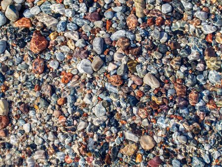 small multicolored stones under water as abstract background outdoor on sunny day