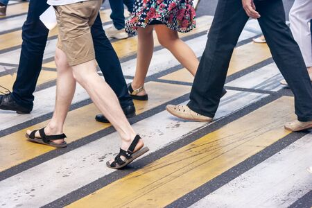 legs of pedestrians walking on the crosswalk in the city on summer day