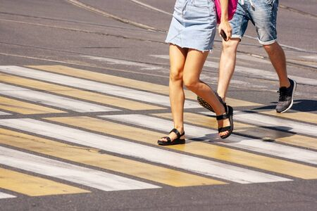legs of young pedestrians walking on the crosswalk in the city on summer day