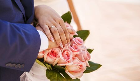 hands of the bride and groom with rings and a bouquet of pink roses outdoor closeup