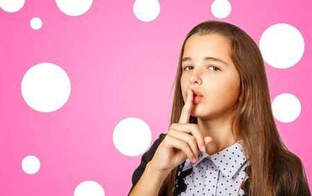 beautiful brunette teen girl with long hair gestures quietly on pink background 版權商用圖片