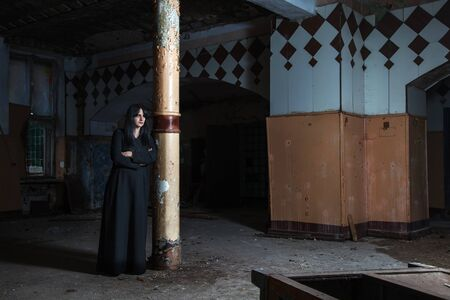 gothic brunette woman stands leaning against a pillar in large empty hall of dark gloomy abandoned house Stok Fotoğraf