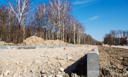 construction of a new modern road in the forest on sunny spring day closeup