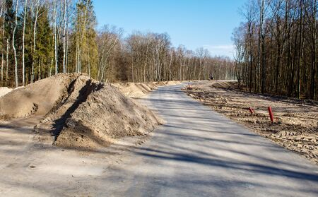 construction of a new modern road in the forest on sunny spring day