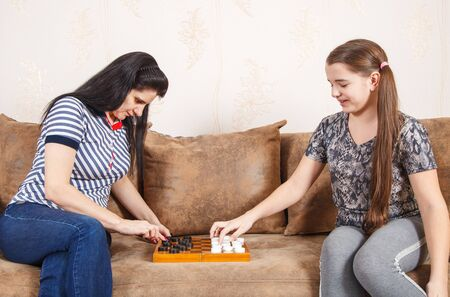 mom and daughter play checkers while sitting on a sofa at home. coronavirus quarantine