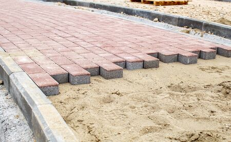 construction of a new modern sidewalk made of tiles outdoor on sunny day