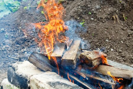 sawn wooden bars burn in a fire outdoor closeup