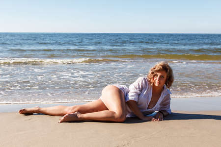 young blonde woman in a wet white shirt lying on the sand of the sea beach on sunny summer day