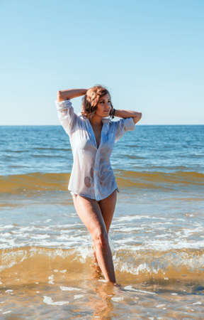 young blonde woman in a wet white shirt standing in the water near the seashore with her hands behind her head on sunny summer day