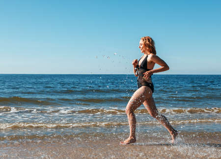 young beautiful blonde girl in a black swimsuit running along the sand of the sea shore on sunny summer day Standard-Bild - 152231831