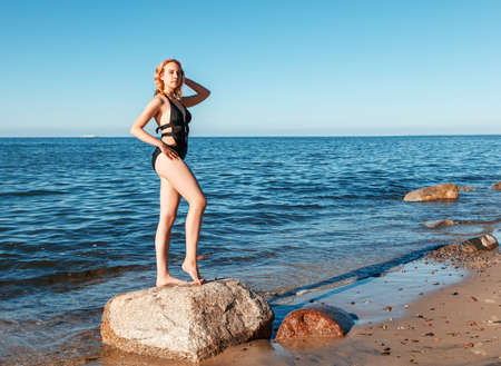 young beautiful blonde girl in a black bathing suit standing on a large stone of the sea shore with her hand behind her head on sunny summer day