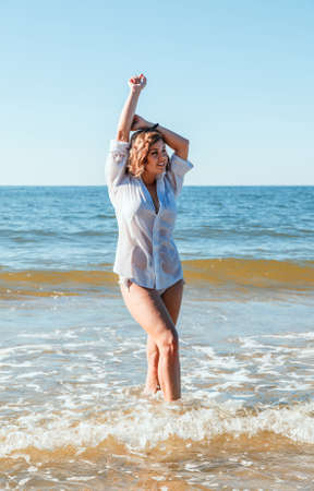 young blonde woman in a wet white shirt standing in the water near the seashore with her hands behind her head on sunny summer day Standard-Bild