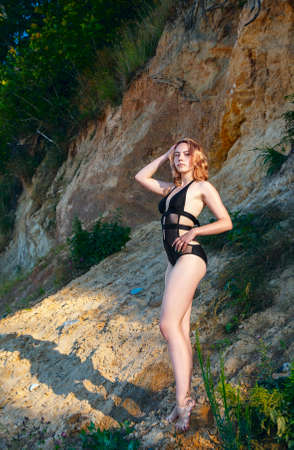 young beautiful blonde girl in a black swimsuit standing under a large cliff of the sea shore with her hand behind her head on sunny summer day Standard-Bild
