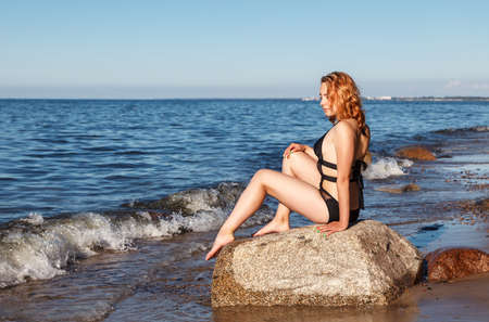 young beautiful blonde girl in a black bathing suit sitting on a large stone of the sea shore on sunny summer day Standard-Bild - 152231854
