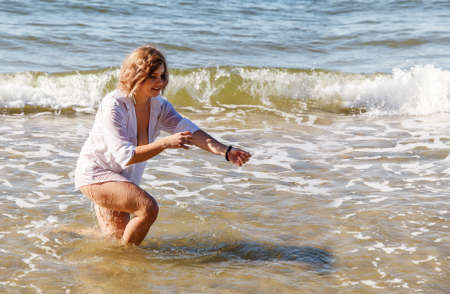 young blonde woman in a wet white shirt sitting in the water near the seashore on sunny summer day Standard-Bild