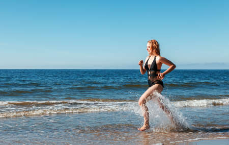 young beautiful blonde girl in a black swimsuit running along the sand of the sea shore on sunny summer day Standard-Bild