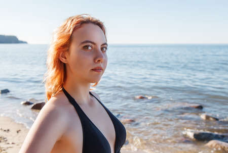 portrait of young beautiful blonde girl in a black bathing suit posing on a sea shore on sunny summer day Standard-Bild