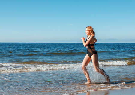 young beautiful blonde girl in a black swimsuit running along the sand of the sea shore on sunny summer day Standard-Bild - 152231865