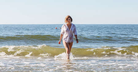 young blonde woman in a wet white shirt coming out of the water near the seashore on sunny summer day Standard-Bild - 152231864