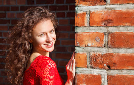 portrait of a young beautiful brunette girl in a red dress near old brick wall on sunny summer day outdoor closeup