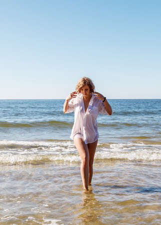 young blonde woman in a wet white shirt coming out of the water near the seashore on sunny summer day