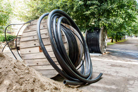 two large wooden industrial reels with cable in city street on sunny summer day Standard-Bild