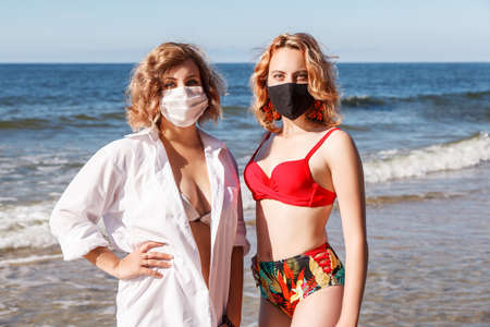two young blonde girls in a swimsuits and protective masks standing on the seashore on sunny summer day closeup Standard-Bild - 152231873