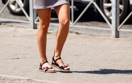 young woman walking on the sidewalk on sunny summer day. legs closeup Standard-Bild - 152232395