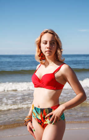 young blonde girl in a red swimsuit standing on the seashore on sunny summer day