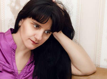 portrait of a young beautiful brunette woman in a crimson blouse indoor closeup Standard-Bild