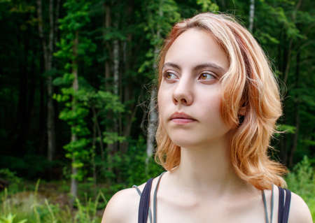 portrait of a young beautiful blonde girl in the park on summer day closeup