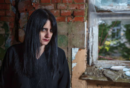 portrait of young beautiful goth woman in black dress standing near broken window in an abandoned house closeup