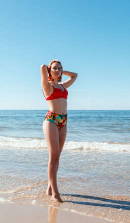 young blonde girl in a red swimsuit standing on the seashore with her hands behind her head on sunny summer day Standard-Bild - 152232915