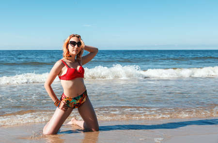 young blonde girl in a red swimsuit and sunglasses standing on the seashore with her hand behind her head on sunny summer day Standard-Bild