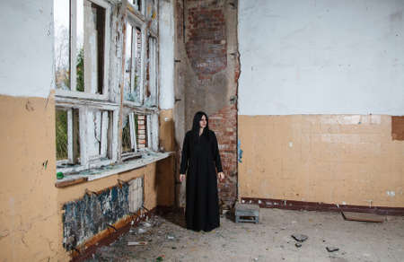 young beautiful goth woman in black dress standing near broken window in an abandoned house