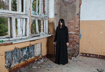 young beautiful goth woman in black dress standing near broken window in an abandoned house Standard-Bild - 152232930